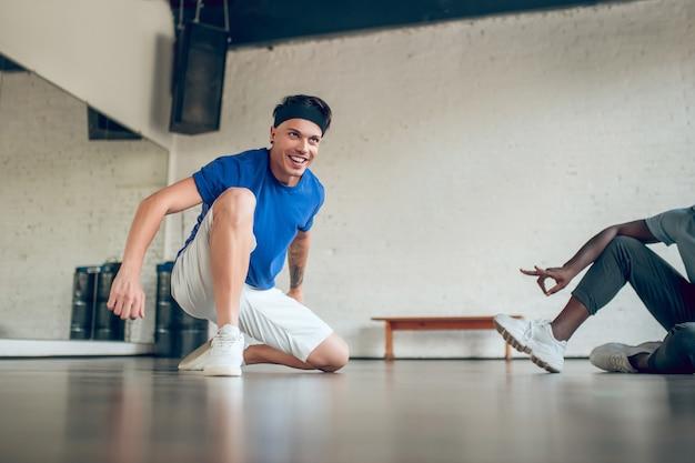 훌륭한 결과. 바닥에 무릎을 만지고 머리 띠에 행복 한 젊은 웃는 남자