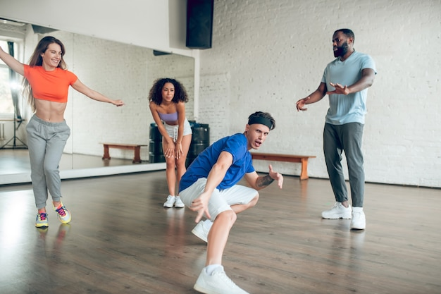 Excellent result. young sporty emotional guy in headband dancing squatting stretching out his leg in circle of friends in dance hall