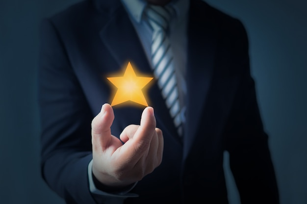 Excellent service and best customer experience or good client , business man showing star rating or goal on dark blue background