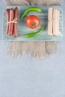 素晴らしいおやつ。ゆでソーセージとサラミと野菜。