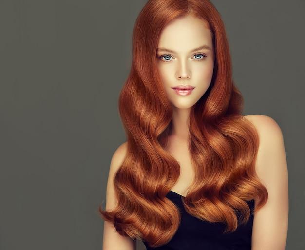 赤い光沢のある手入れの行き届いた長い髪の優れた波は、若い素敵なモデルのかわいい顔を囲んでいますヘアケアと理髪アート
