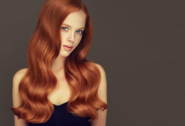 赤い光沢のある手入れの行き届いた長い髪の優れた波が若い素敵なモデルのかわいい顔を囲んでいますヘアケアと理髪アート