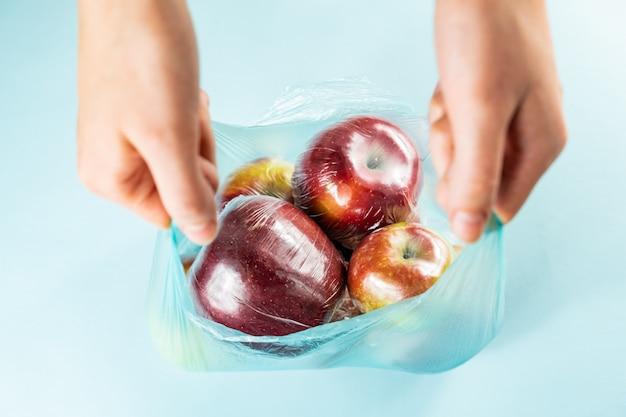 Концепция чрезмерного использования пластика: свежие яблоки в кухонной упаковке в полиэтиленовый пакет.