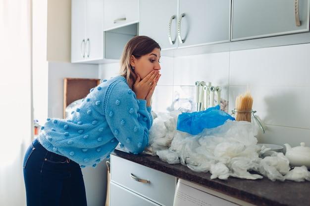Чрезмерное использование пластиковых пакетов. шокированная женщина собрала кучу использованных полиэтиленовых пакетов на кухне дома