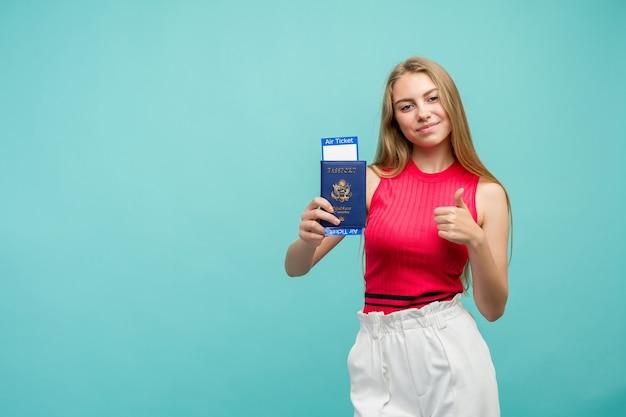 교환 학습 개념. 티켓과 여권을 들고 꽤 젊은 학생 여자의 스튜디오 초상화. 밝은 파란색 배경에 고립.