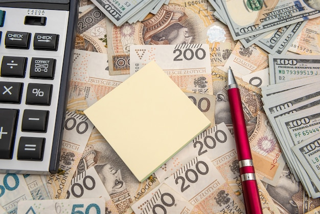 달러와 폴란드 즐로티 지폐 사이의 환율. 계산기와 펜과 메모