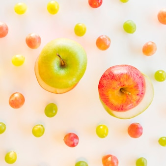 Exchange slices of green and red apple surrounded with grapes on white backdrop