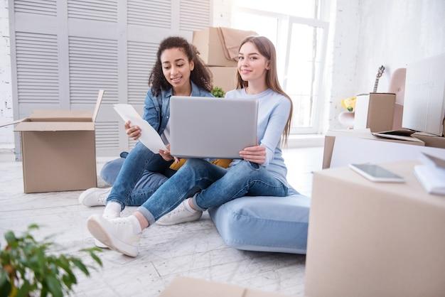 Обмен идеями. красивые молодые девушки сидят на полу и обсуждают идеи относительно декора стен, просматривая таблицы цветов