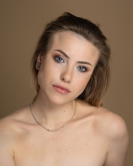Excite girl with heterochromia, nose piercing and plug in one ear, and strange hairstyle. she has amazing professional makeup and silver chain around her neck. beige background. studio shot