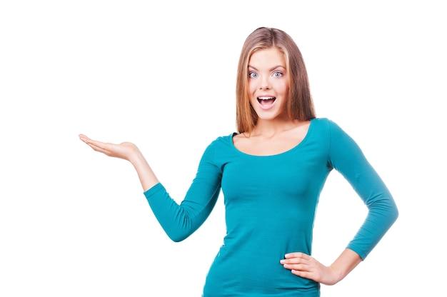 興奮して...コピースペースを保持し、白い背景に立っている間驚いて見える美しい若い女性