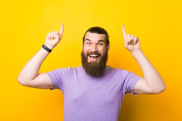 このオファーに興奮しました。ひげを生やした男は黄色の背景の上に上向きです。