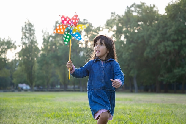 Excited adorable black haired girl holding pinwheel and running on grass in park. children outdoor activity concept