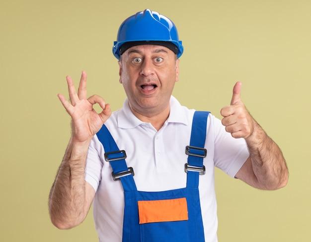 Взволнованный взрослый человек-строитель в униформе жестами жест рукой и большими пальцами руки вверх изолирован на оливково-зеленой стене