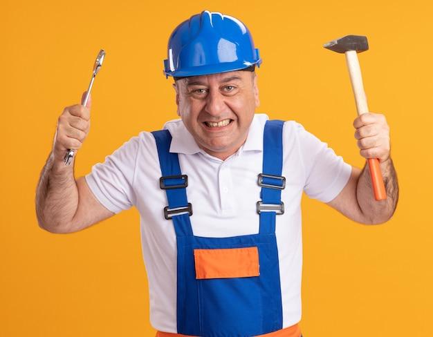 L'uomo adulto eccitato del costruttore in uniforme tiene la chiave e il martello isolati sulla parete arancione
