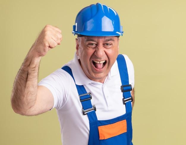 Uomo adulto emozionante del costruttore in uniforme che alza il pugno su verde oliva