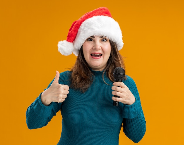 Excited adult caucasian woman with santa hat thumbs up and holds mic isolated on orange background with copy space