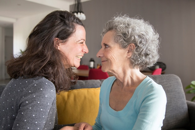 Excited adult daughter spending time with senior mother at home