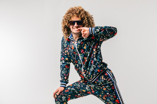 Excited adult funny man in stylish flowered tracksuit smiling and posing for camera over white background.