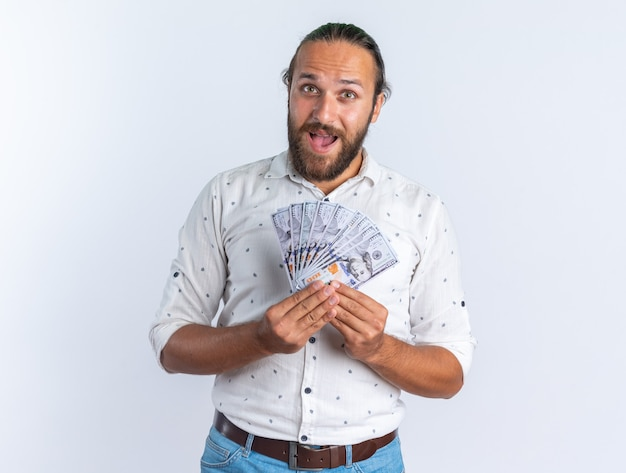 Excited adult handsome man wearing glasses holding money looking at camera isolated on white wall