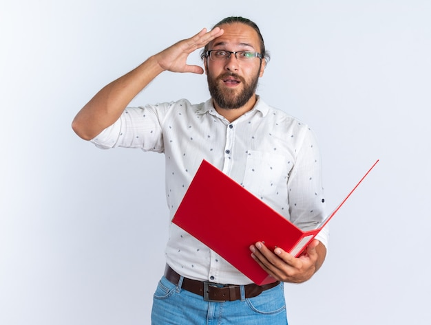 額に手を離して開いたフォルダを保持している眼鏡をかけている興奮した大人のハンサムな男