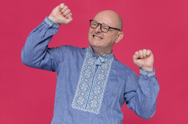 Excited adult man in blue shirt wearing glasses raising fists up