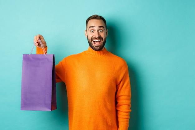 Возбужденный взрослый мужчина держит фиолетовую сумку для покупок и улыбается, собирается в торговый центр, стоя на бирюзовом фоне.