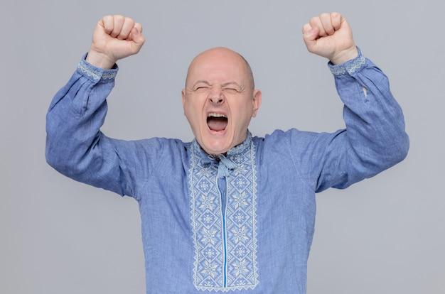 Возбужденный взрослый мужчина в синей рубашке стоит с поднятыми кулаками