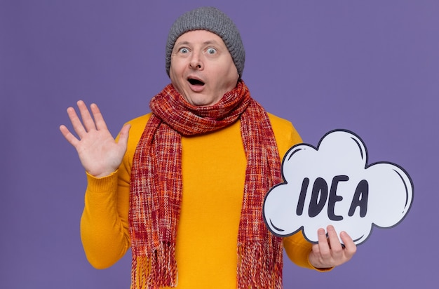 Excited adult man with winter hat and scarf around his neck holding idea bubble