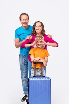 白い背景の上の夫と息子と一緒に旅行中にスーツケースを持つ少年の顔に笑みを浮かべて眼鏡を身振りで示す興奮した大人の母親