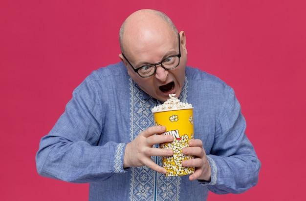 Uomo slavo adulto eccitato in camicia blu che indossa occhiali ottici che tiene e guarda il secchio di popcorn