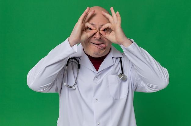 의사 유니폼을 입은 흥분된 성인 슬라브 남자와 청진기가 혀를 내밀고 손가락을 통해