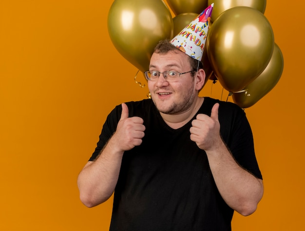 생일 모자를 쓰고 광학 안경에 흥분된 성인 슬라브 남자가 헬륨 풍선 앞에 서서 두 손으로 엄지 손가락을 올립니다.