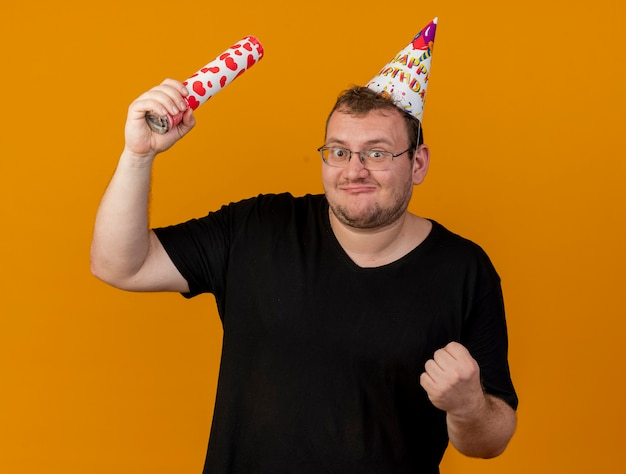 Excited adult slavic man in optical glasses wearing birthday cap holds confetti cannon and keeps fist