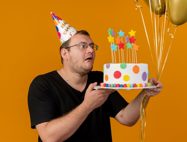 Excited adult slavic man in optical glasses wearing birthday cap holds helium balloons and birthday cake