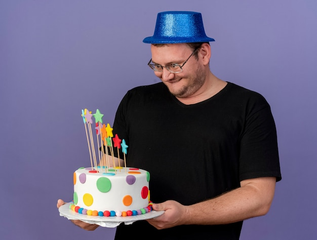 Excited adult slavic man in optical glasses wearing blue party hat holding and looking at birthday cake