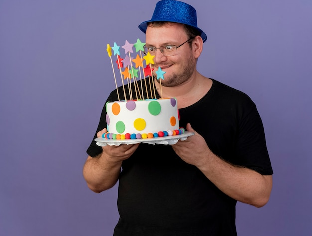 Excited adult slavic man in optical glasses wearing blue party hat holds and looks at birthday cake