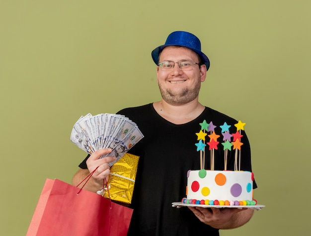 Excited adult slavic man in optical glasses wearing blue party hat holds money gift box paper shopping bag and birthday cake