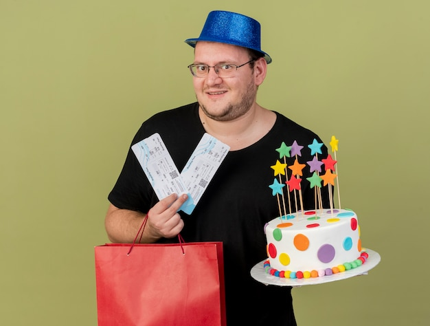 Excited adult slavic man in optical glasses wearing blue party hat holds paper shopping bag birthday cake and air tickets
