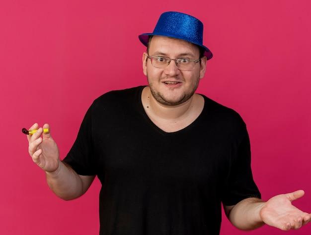 Emozionato uomo slavo adulto in occhiali ottici che indossa un cappello da festa blu tiene un fischio di festa