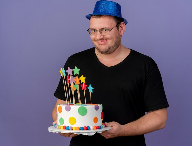 Excited adult slavic man in optical glasses wearing blue party hat stucks out tongue holding birthday cake