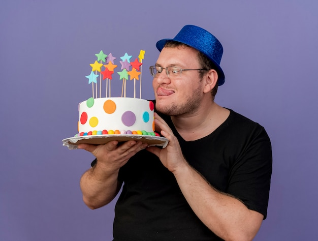 Excited adult slavic man in optical glasses wearing blue party hat stucks out tongue and holds birthday cake
