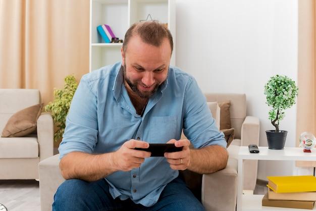 흥분된 성인 슬라브어 남자는 안락의 자에 앉아 거실 내부의 전화를보고