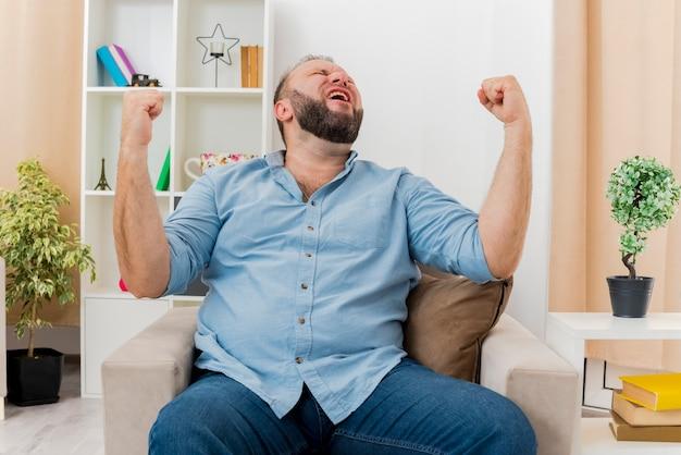 흥분된 성인 슬라브 남자가 안락 의자에 앉아 주먹을 들고 거실 내부를 올려다 보았습니다. 무료 사진