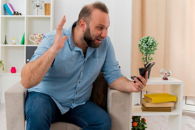 흥분된 성인 슬라브 남자는 안락 의자에 앉아 손을 들고 거실 내부의 전화를보고