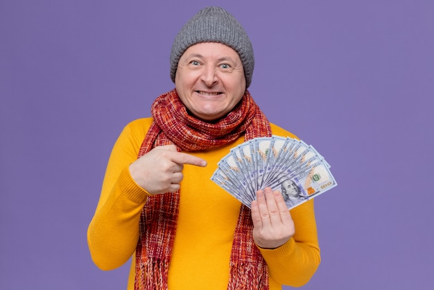 Excited adult slavic man with winter hat and scarf around his neck holding and pointing at money