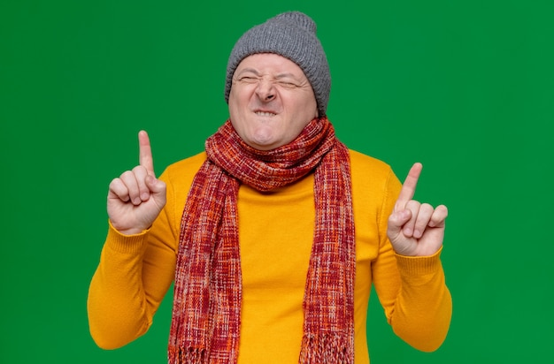 Excited adult slavic man with winter hat and scarf around his neck pointing up