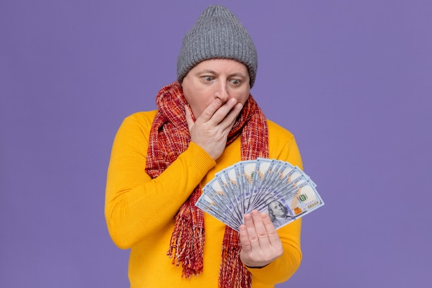 Excited adult slavic man with winter hat and scarf around his neck putting hand on his mouth holding and looking at money