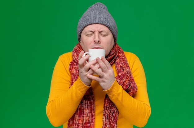 Excited adult slavic man with winter hat and scarf around his neck sniffing cup