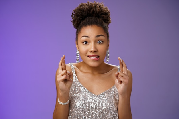 흥분한 아프리카계 미국인 소녀는 은색 드레스 파란색 배경에 낙천적인 흥분으로 서 있는 열렬한 승리 크로스 손가락 행운을 물고 입술 욕망 기대 소원을 빌고, 열망 선물을 받고 흥분.