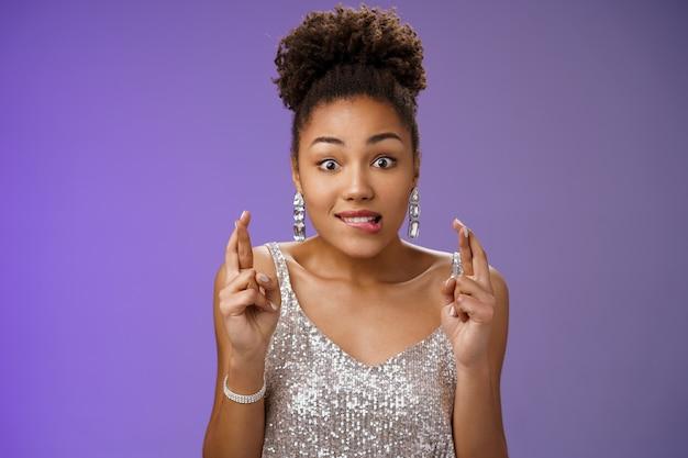 Eccitata ragazza afro-americana eccitata desiderosa di vincere le dita incrociate buona fortuna mordere il labbro desiderio anticipazione che esprime desiderio, desiderosa di ricevere un regalo, ottimista in piedi entusiasta in abito d'argento sfondo blu.